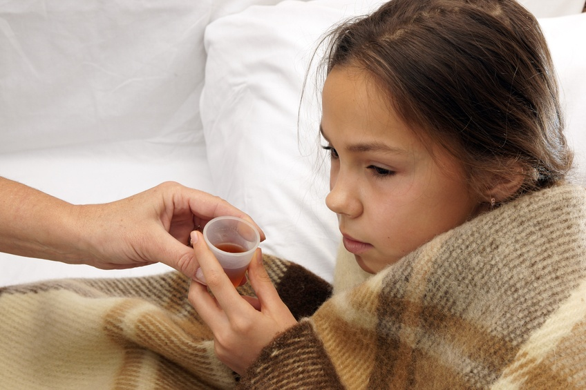 Girl taking cough syrup in bed