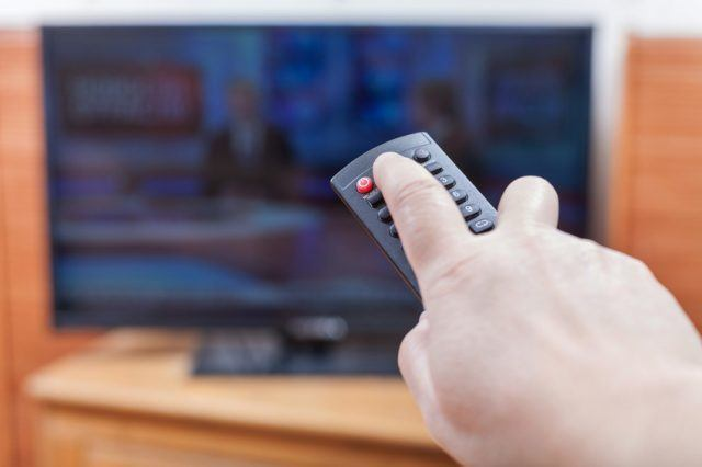 hand reaching for the off button on a remote to turn off the TV