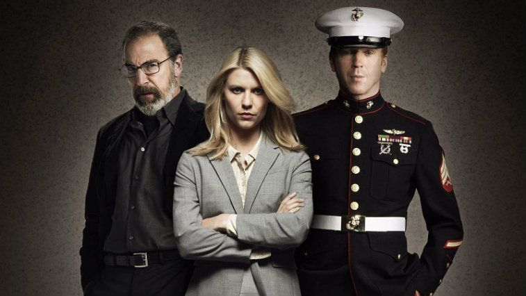 Homeland's Saul, Carrie, and Brody pose in front of a grey background