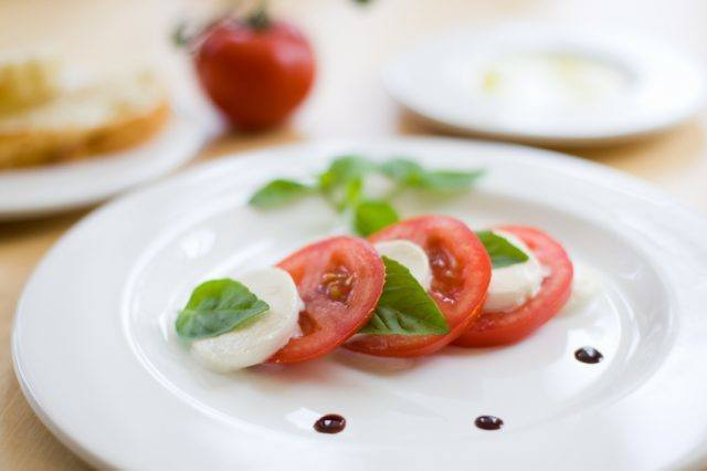 small caprese salad on a white plate with basil and balsamic vinegar