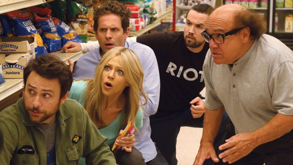 The It's Always Sunny in Philadelphia gang crouches down in a store and looks around a corner