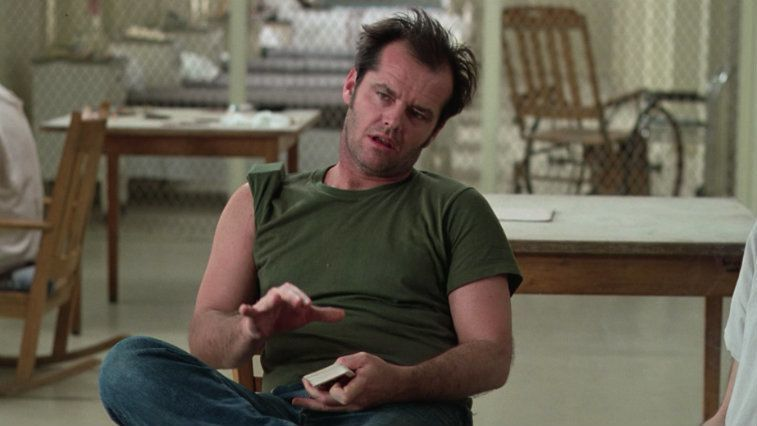Jack Nicholson sitting in a chair with cards in his hand in One Flew Over the Cuckoo's Nest