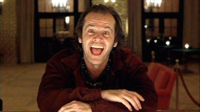 Jack Nicholson in the Shining, sitting at a bar and smiling manically