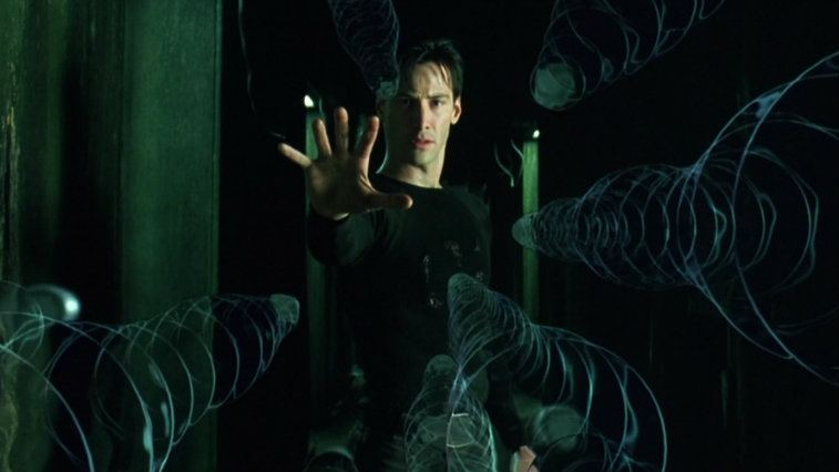 Keanu Reeves has his hand up to stop bullets mid-air in The Matrix