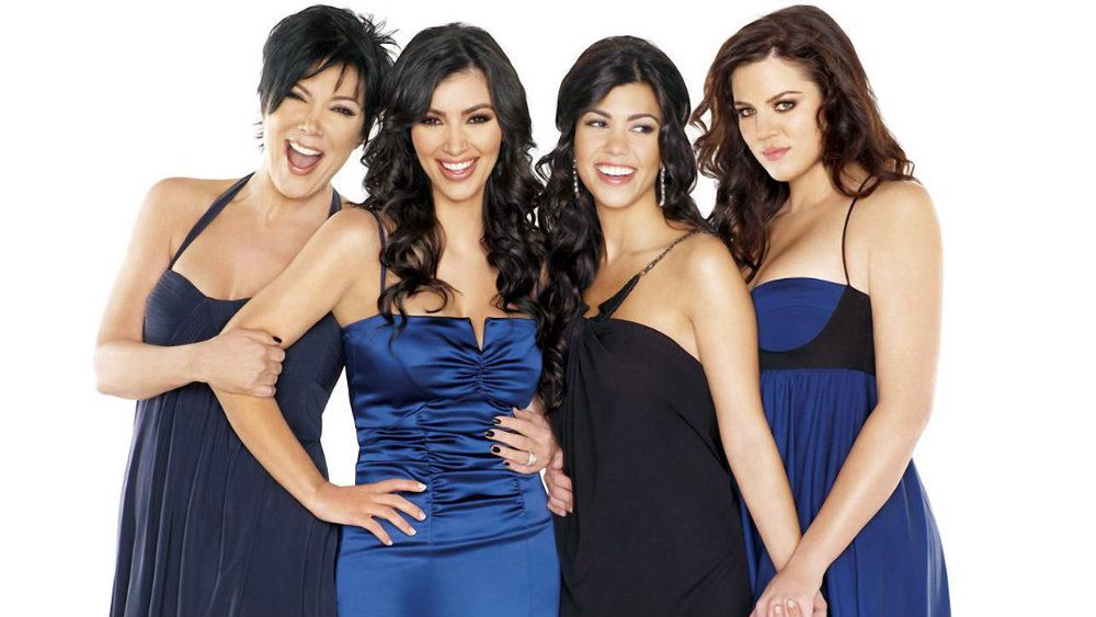 Kris Jenner, Kim, Kourtney, and Khloe Kardashian pose together in blue and black dresses.