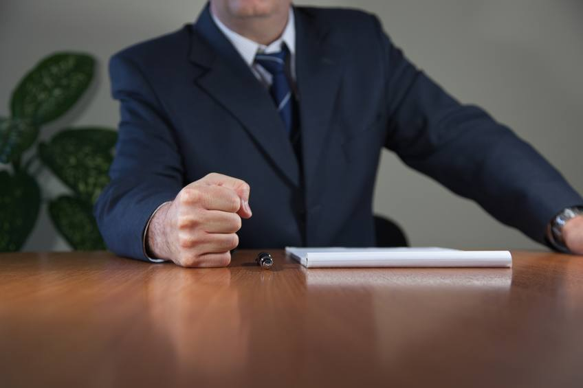 a man in office puts fist on the table