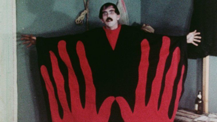 Man in a black and red outfit with giant hands printed on it from Manos: The Hands of Fate