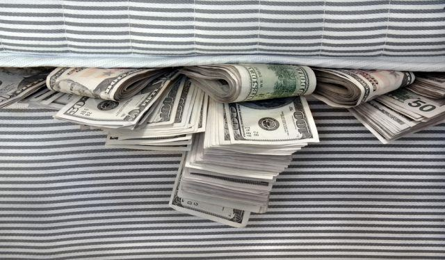 Wads of 50 and 100 dollar bills stuffed under a mattress