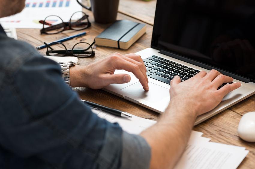 man working on laptop on office desk