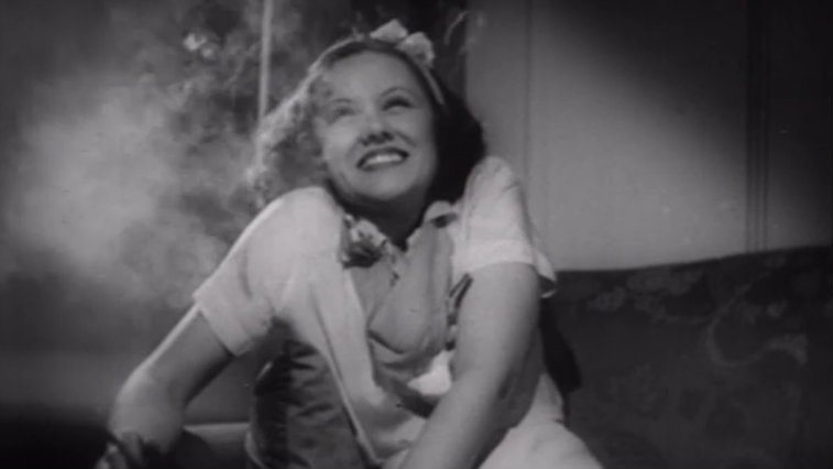 Woman smiling in a room filled with smoke in Reefer Madness