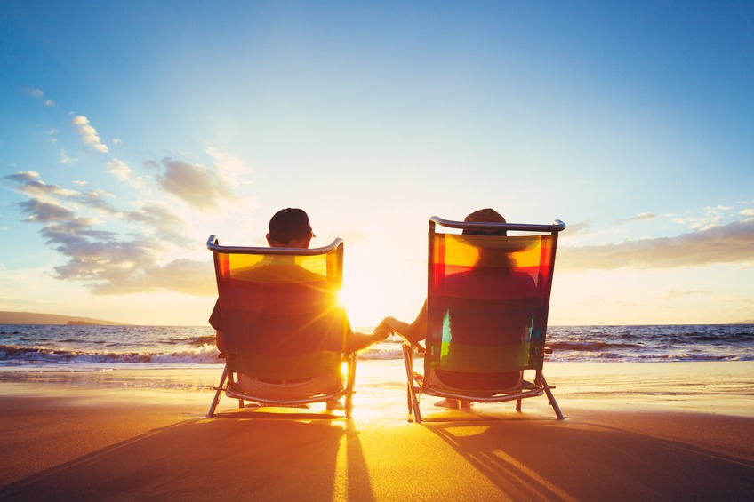 couple in chairs on the beach looking at a sunset, celebrating retirement