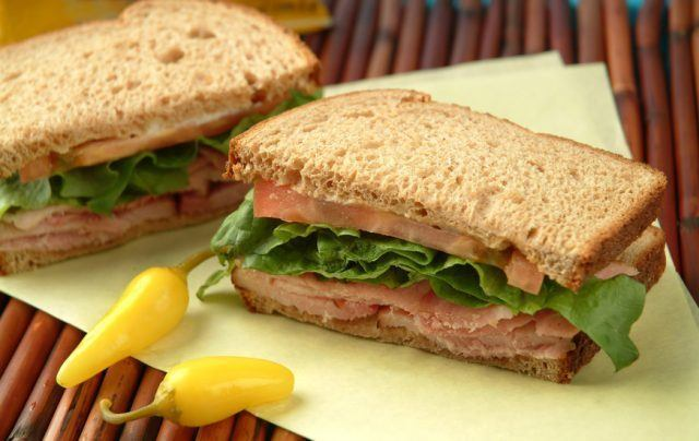 turkey sandwich with lettuce and tomatoes cut in half