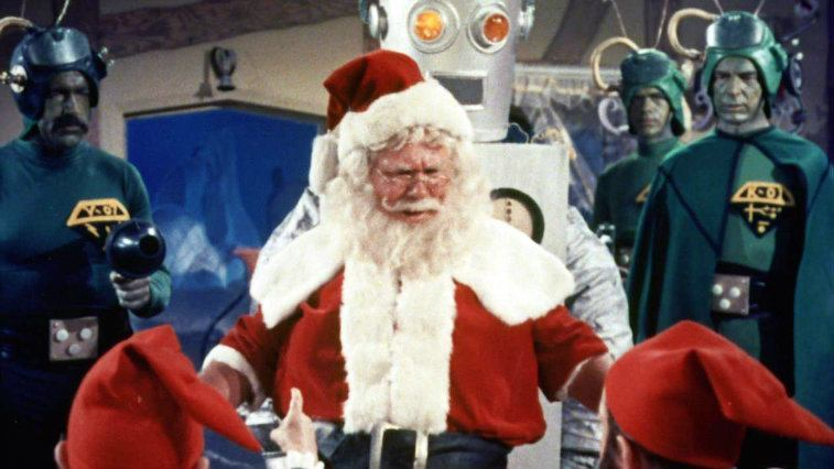 Santa Claus talks to his elves as martians look on