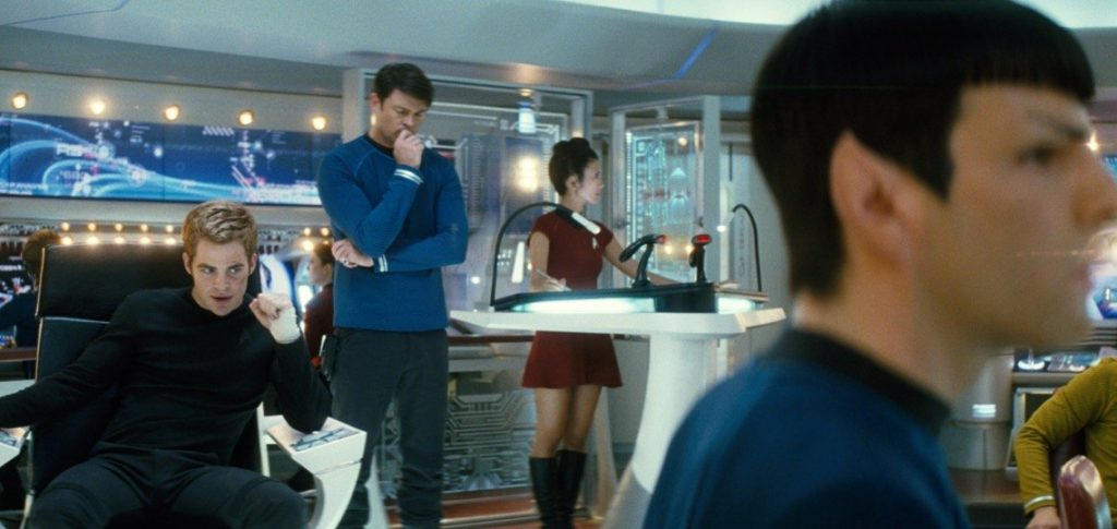 Kirk looks down while sitting the captain chair, while the rest of the crew works on the bridge