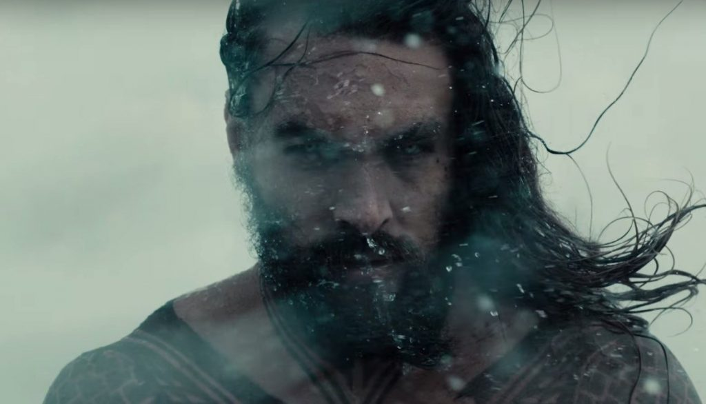 Aquaman stands in the snow looking into the camera