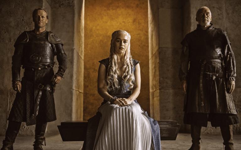 Emilia Clarke sitting next to two men on Game of Thrones.