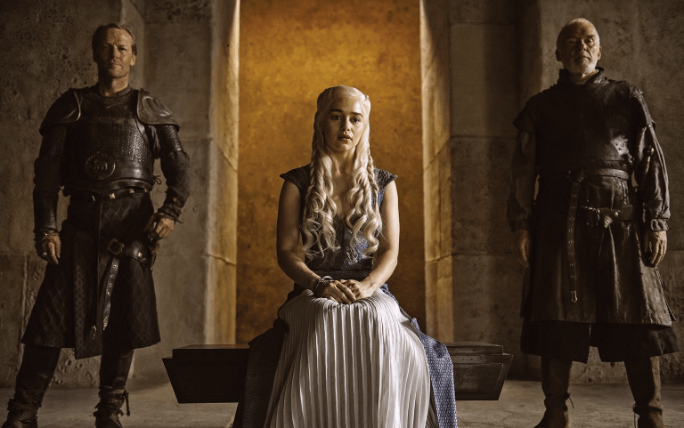 Emilia Clarke sitting next to two men on Game of Thrones.