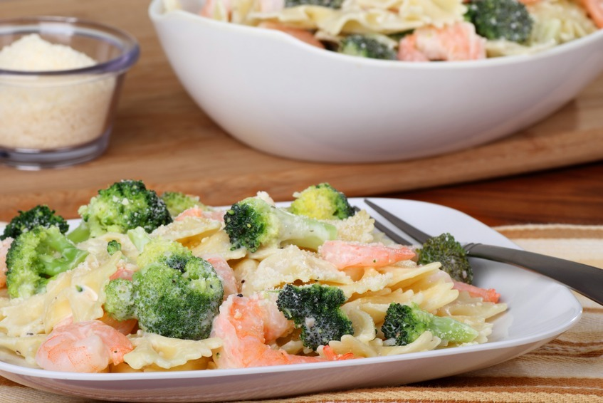 Shrimp with pasta and broccoli with a sauce on a plate