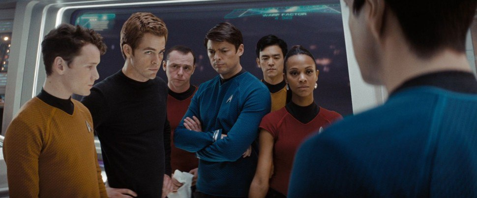 The cast of Star Trek stands together on the bridge of the Enterprise