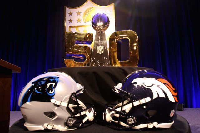 Two football helmets in front of a trophy.
