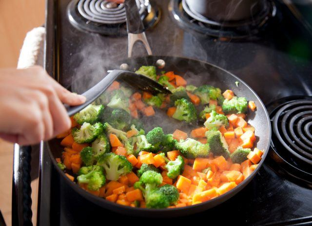 cooking sweet potatoes and broccoli in a skillet