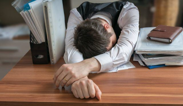 man sleeping on an office desk