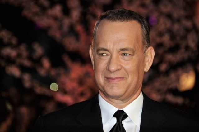 Tom Hanks smiling in a black suit and tie.