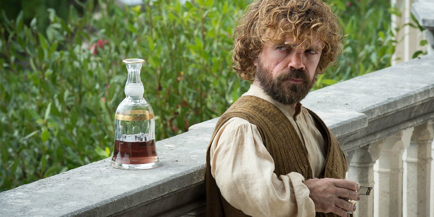 Tyrion Lannister leaning against a railing, with a carafe of wine sitting next to him