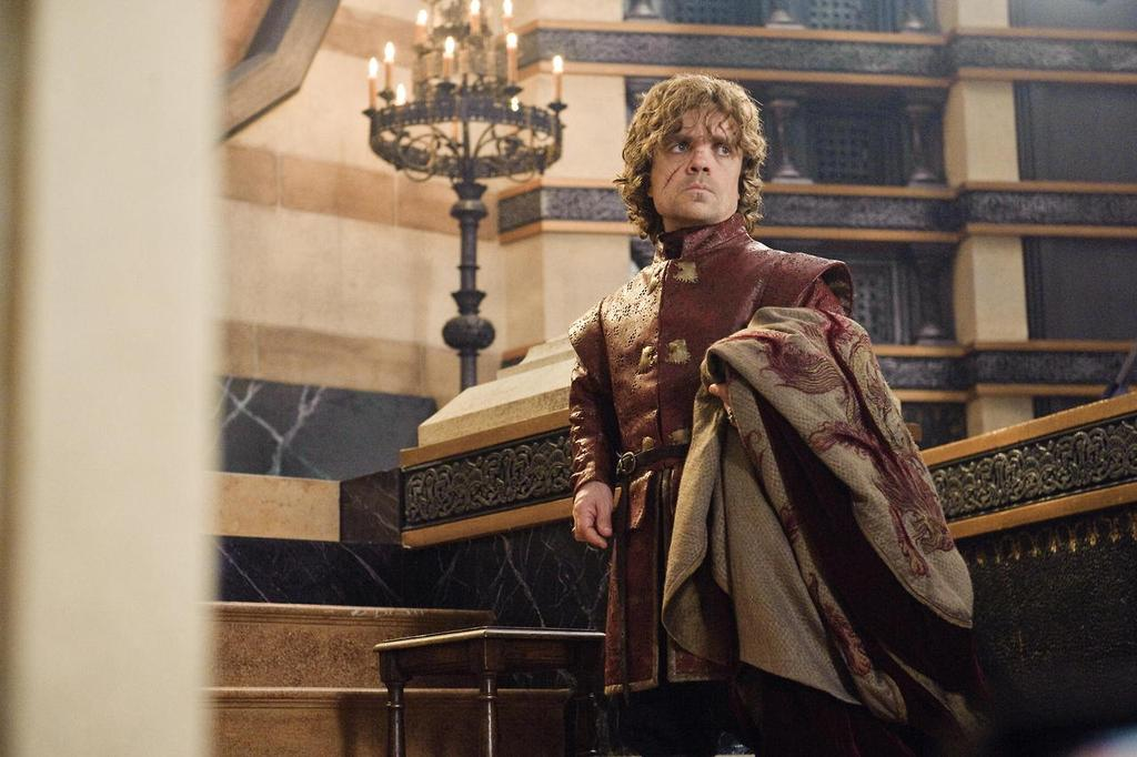 Tyrion Lannister, holding a cloak, wearing red, and looking off to his left