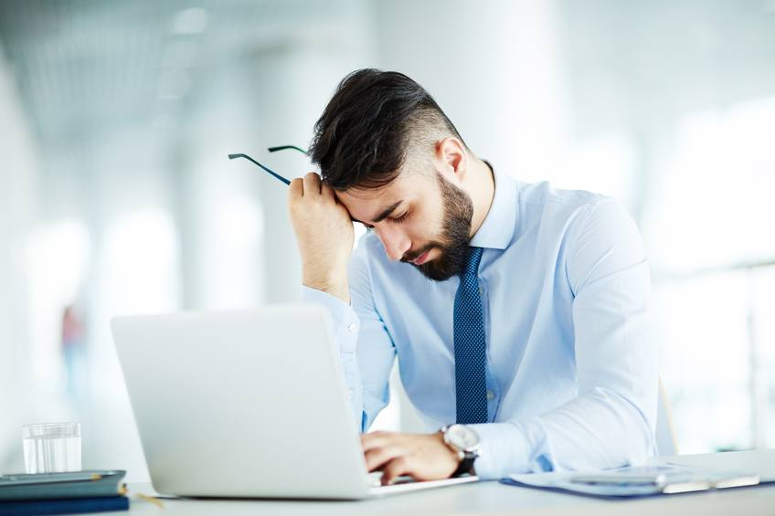not happy at work, tired man in office in front of laptop
