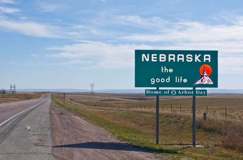 Welcome to Nebraska sign board on a empty road