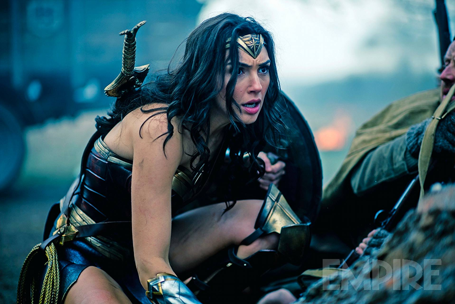 Wonder Woman, played by Gal Gadot, crouching on a battlefield
