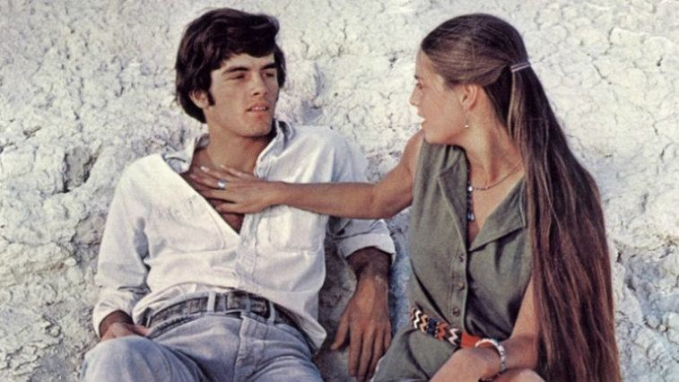 Two characters on Zabriskie Point sit and speak together