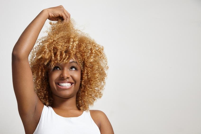 black woman looking at her hair