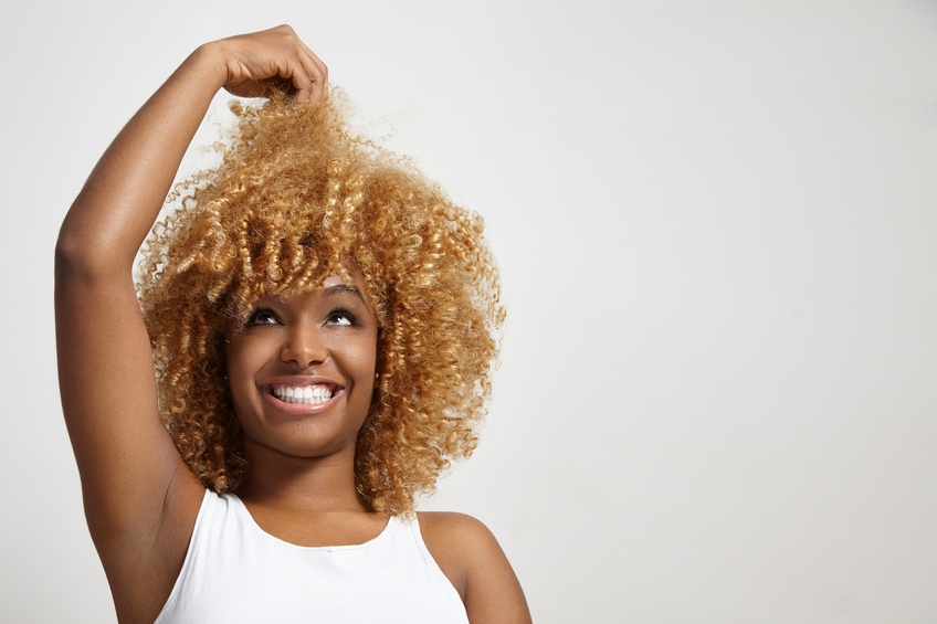black woman looking at her hair