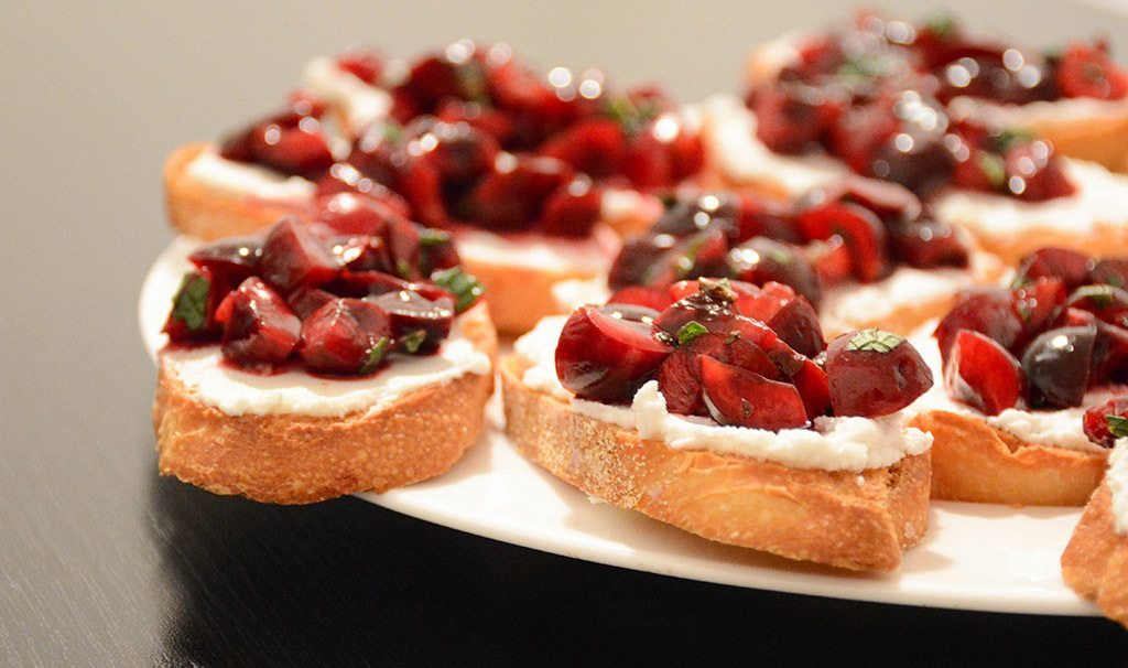 white plate filled with cherry and goat cheese crostini