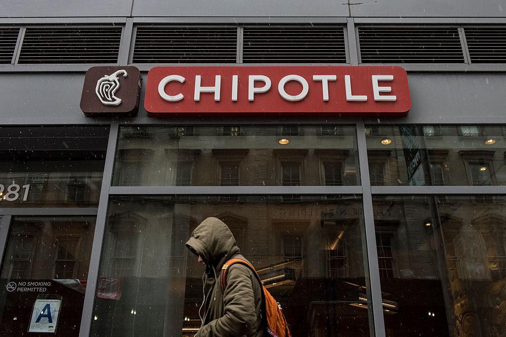 A man walks past a Chipotle restaurant