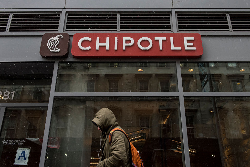 A man walks past a Chipotle restaurant