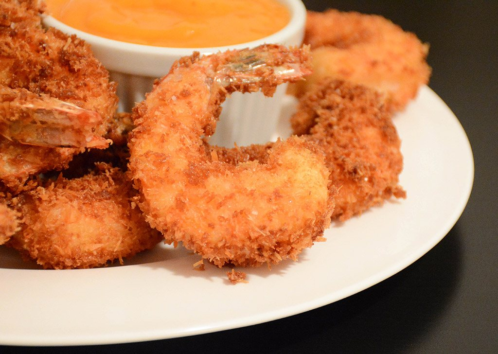 detail of crispy coconut shrimp served with mango sauce