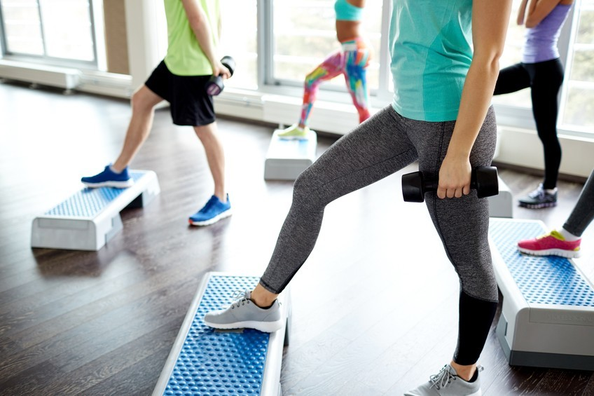 fitness class stepping onto benches with dumbbells