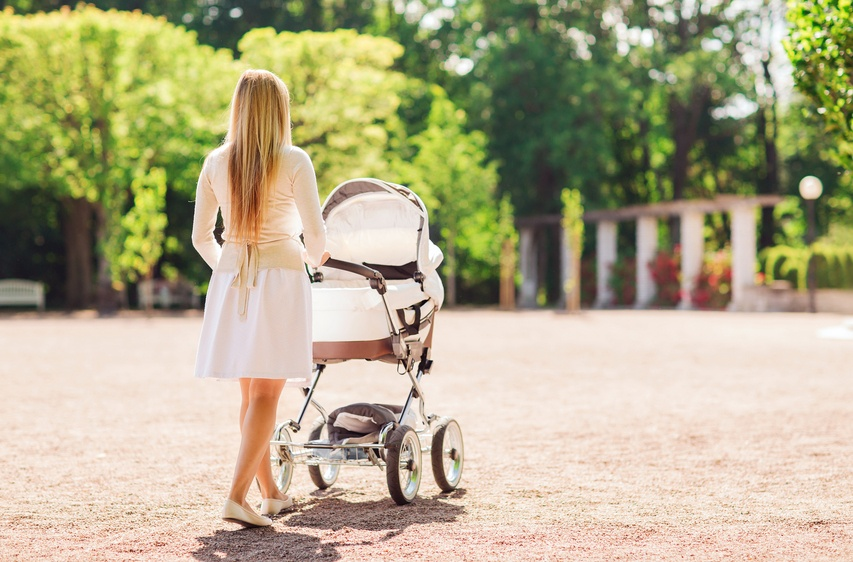 young mother pushing a stroller as she walks