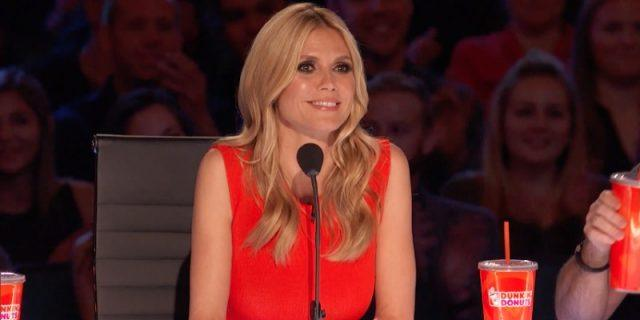 Heidi Klum sitting in front of a microphone at a judge's table.
