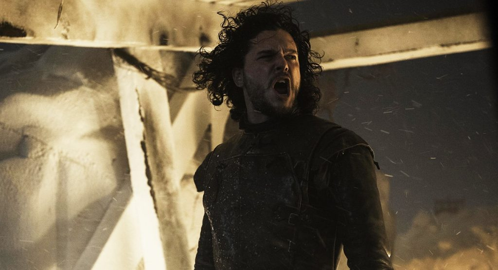 Jon Snow is yellowing in front of something on fire.