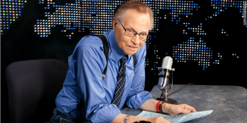 Larry King sits as his desk and leans into a microphone on Larry King Live.