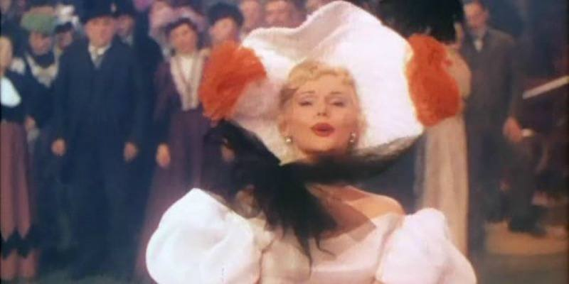 Zsa Zsa in a white dress and hat on Moulin Rouge
