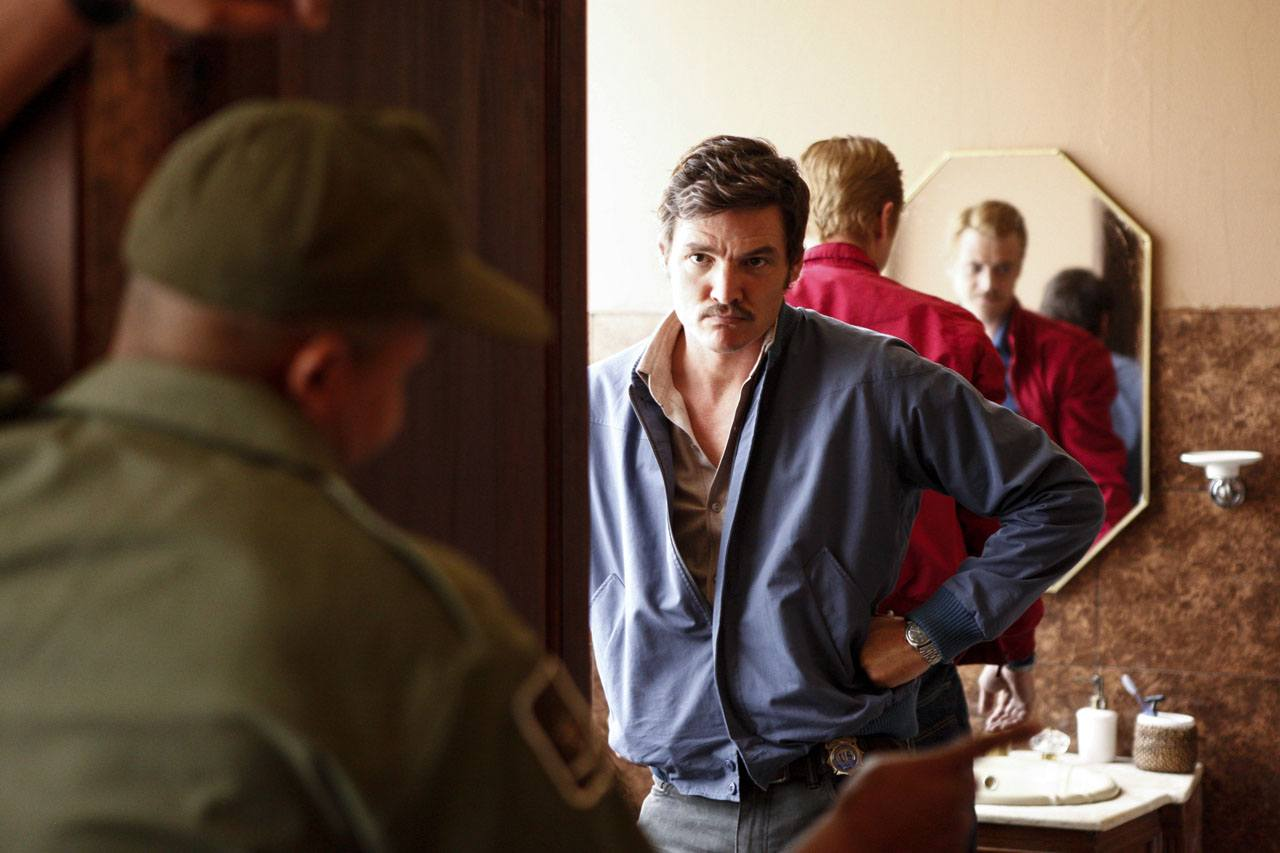 Javier Pena stands in a doorway talking to a police officer in Narcos