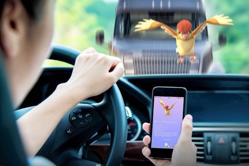 A man drives while playing Pokemon GO.