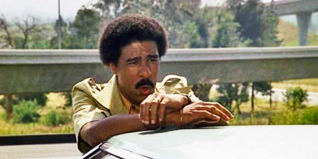 richard pryor in Silver Streak standing behind a car and making a face