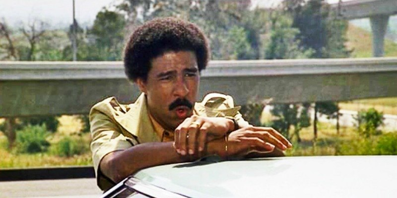 Richard Pryor is leaning against a car in Silver Streak
