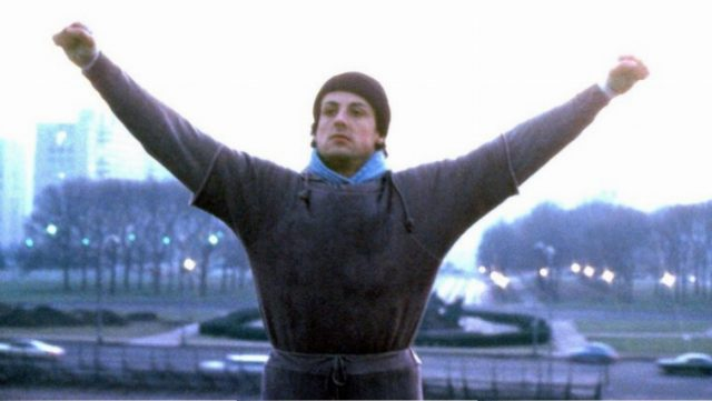 Rocky is at the top of the steps with his arms up in the air.